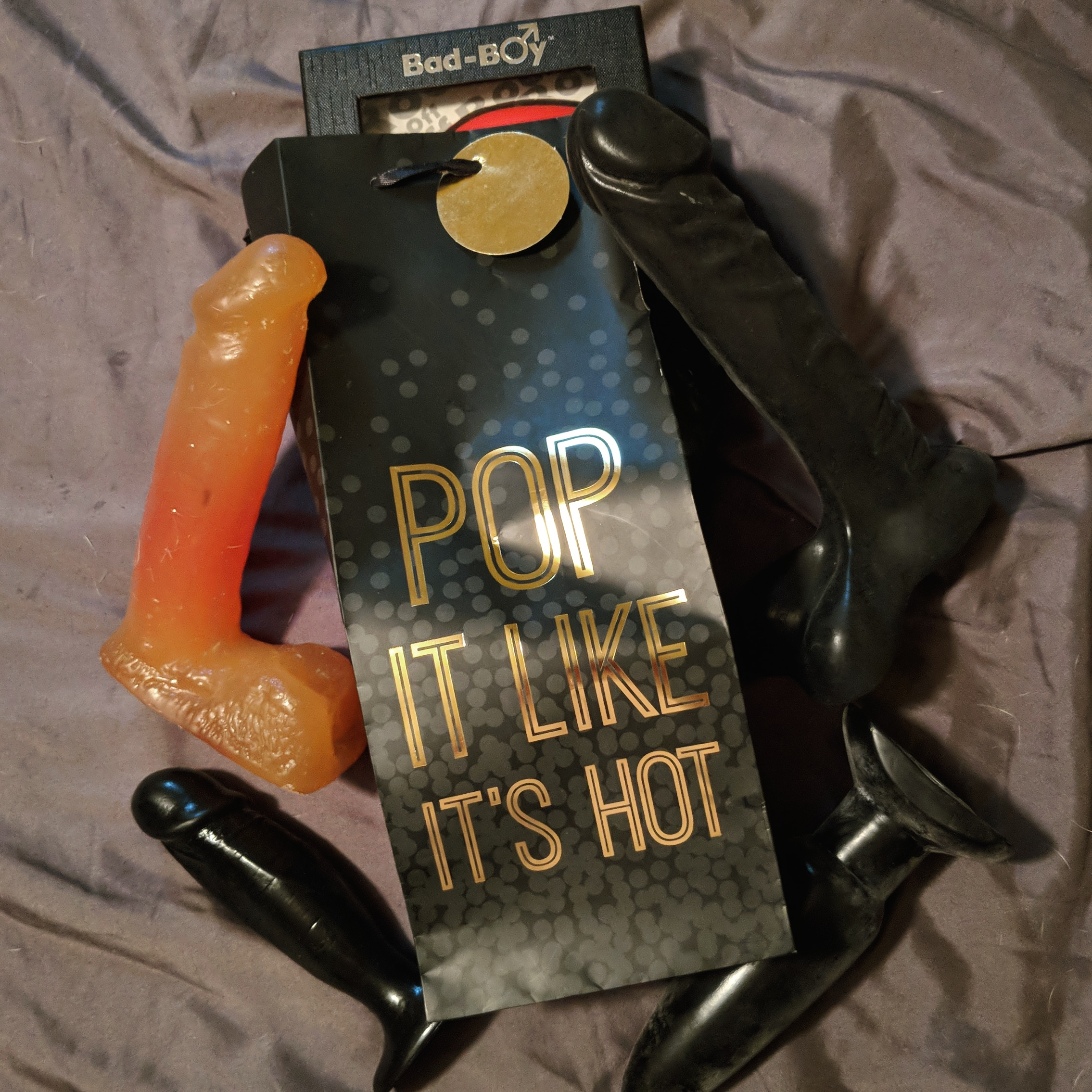 "a bag reading ""pop it like its hot"" surrounded by dildo and buttplugs"